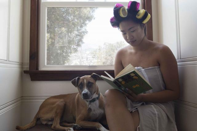 girl with dog reading book by window