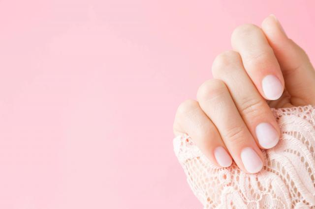 Beautiful, perfect, groomed woman's hand with light pink nails on the pastel background. Manicure, pedicure beauty salon concept