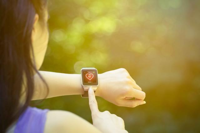 Female runner checking heart rate on smart watch outdoors