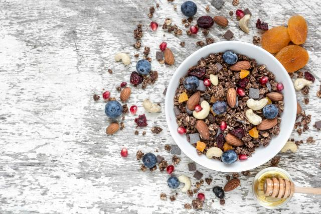 bowl of chocolate oat granola or muesli with nuts, berries, dried fruits and honey