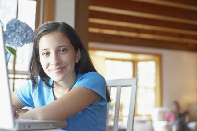 Portrait of a teenage girl leaning on a laptop