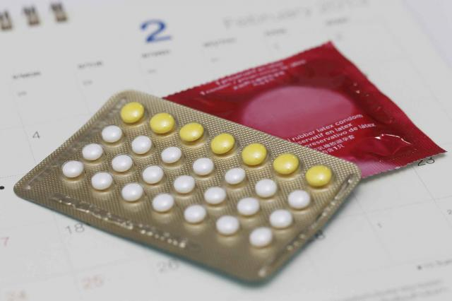 birth control pills with condom on a calendar