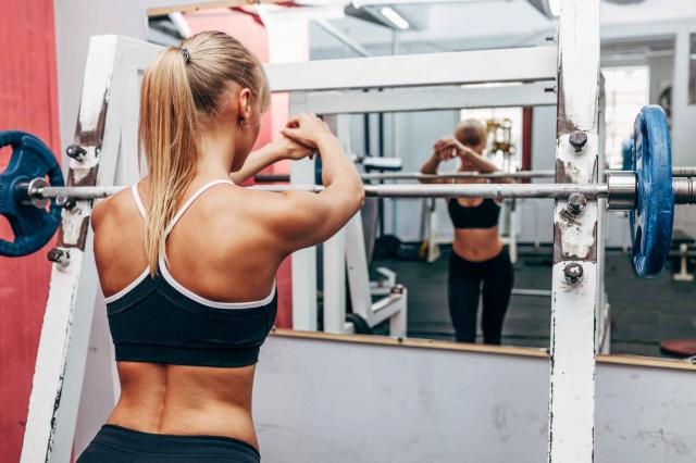 fitness woman preparing barbell squats in a gym