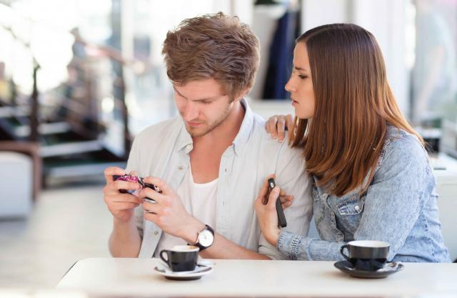 Frustrated young woman asking her boyfriend to stop playing with phone