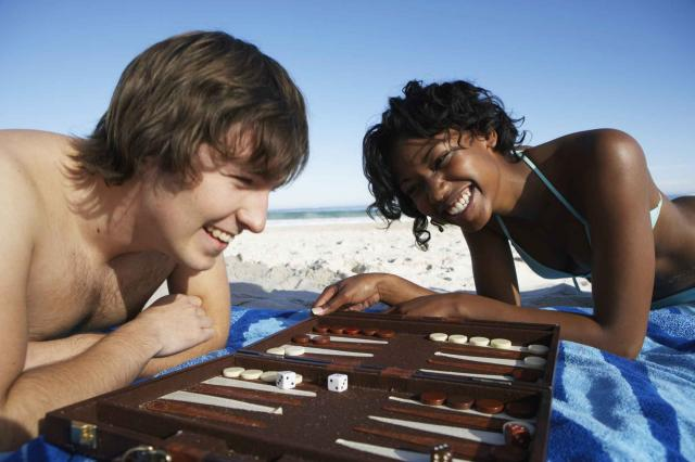 Teenage couple (16-18) on beach, playing backgammon, laughing