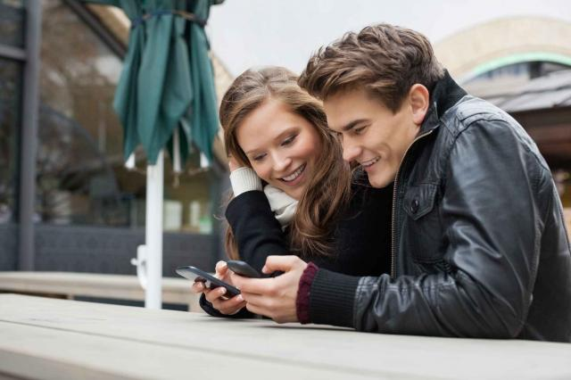 Couple Using Mobile Phone While Leaning On Bench