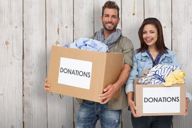 Smiling young couple with donation box
