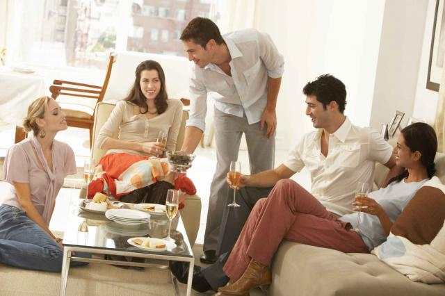 Group of young people gathered around coffee table, drinking champagne