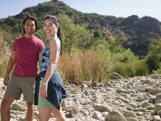 Smiling young couple walking in dry riverbed