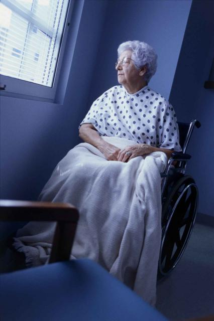 Female patient sitting in a wheelchair looking out of a window
