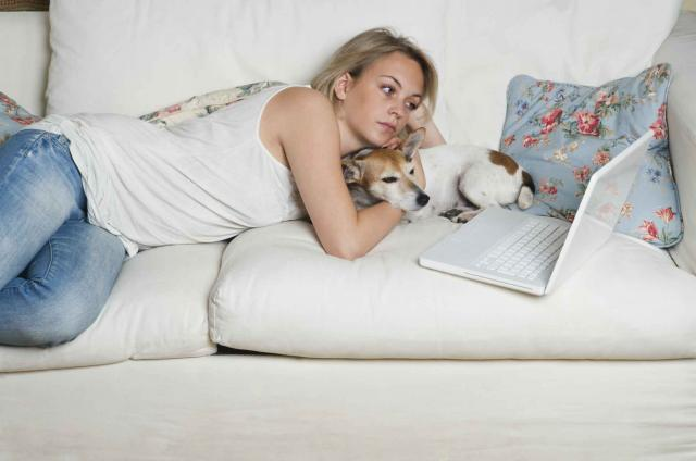 Young woman lying on sofa with dog, looking at laptop