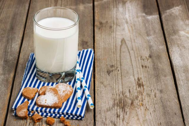 Glass of milk on a rustic wooden table
