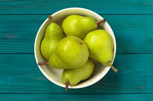 green pears in white bowl on blue wooden background.