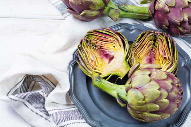 Fresh big Romanesco artichokes green-purple flower heads ready to cook