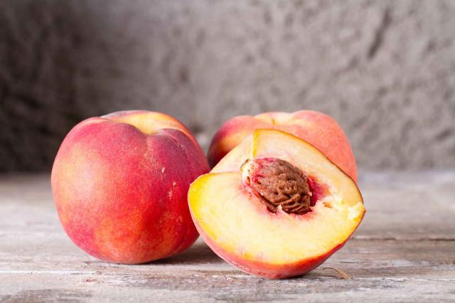 The ripe whole and sliced peaches