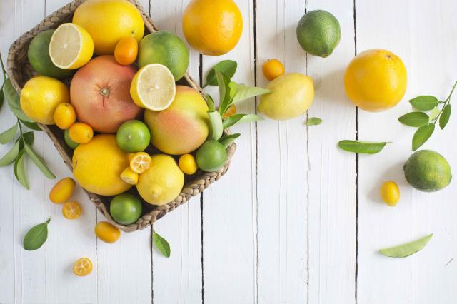 Citrus fruits family on rustic white wooden background. Horizontal view. Text space images.