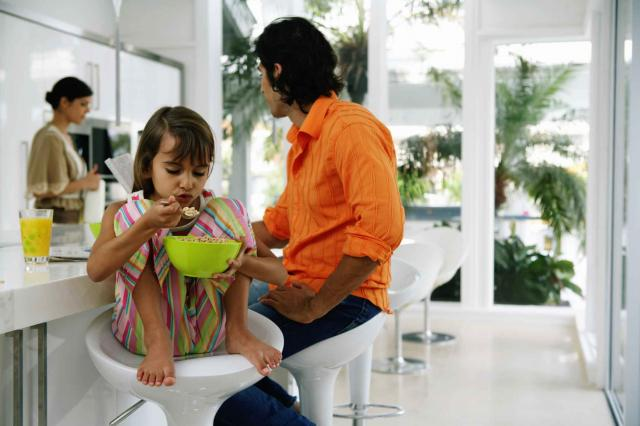 Family at breakfast table, girl (8-10) holding bowl with cereal