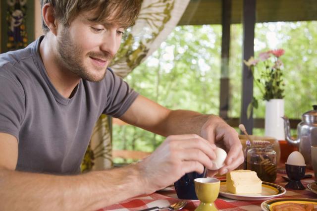 Man peeling shell of hard-boiled egg