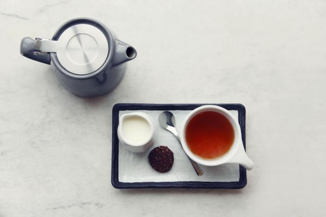 overhead tray of tea, milk and biscuit with teapot