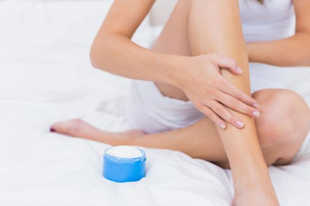 Woman putting some moisturiser