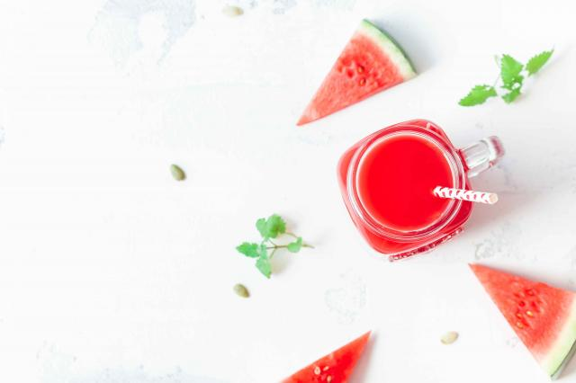 Watermelon juice and watermelon slices on white background