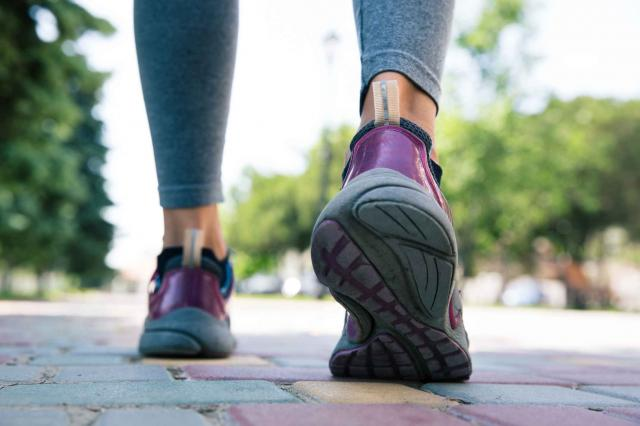 Footwear on female feet running on road