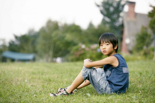 Japanese boy sitting, looking at camera
