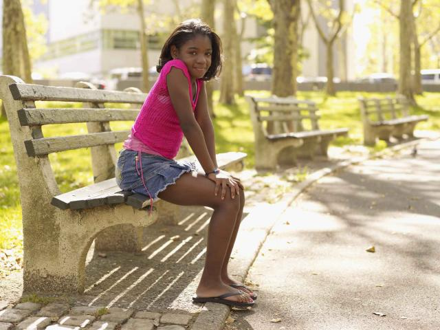 African girl sitting on bench in park
