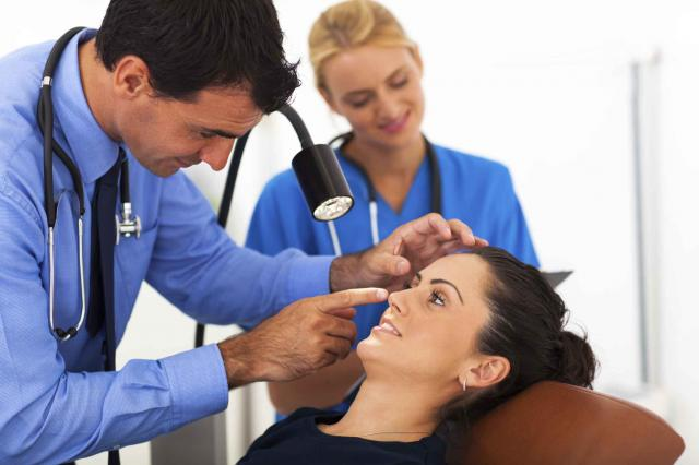 ophthalmologist examining young woman's eye