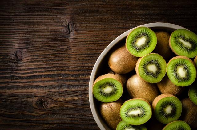Kiwi fruits in bowl over wooden background