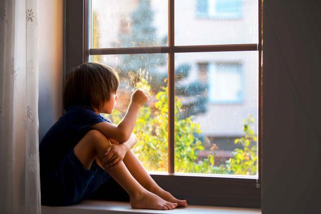 Sad child, boy, sitting on a window ledge