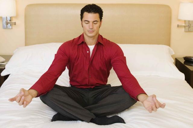 Man meditating in hotel room