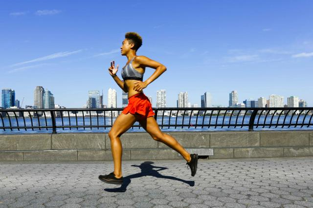 Mixed race woman running at waterfront