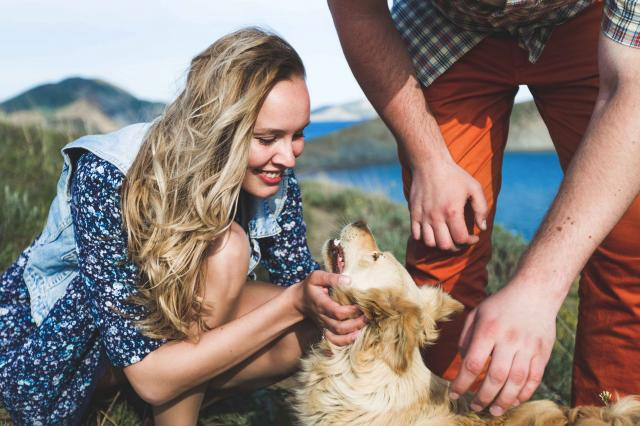 People playing with dog outside by the nature. Happy smile of girl