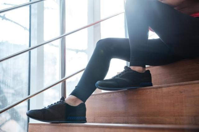 Closeup of legs in black leggings and sneakers of young sportswoman sitting on stairs.