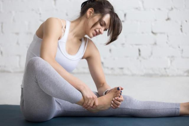 Beautiful young woman feeling pain in her foot during sport workout indoors, close-up