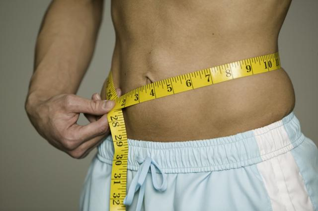 Man measuring waist , mid section