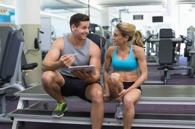 Female bodybuilder sitting with personal trainer talking