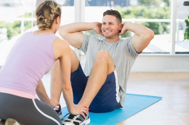 Trainer helping fit man in doing sits up