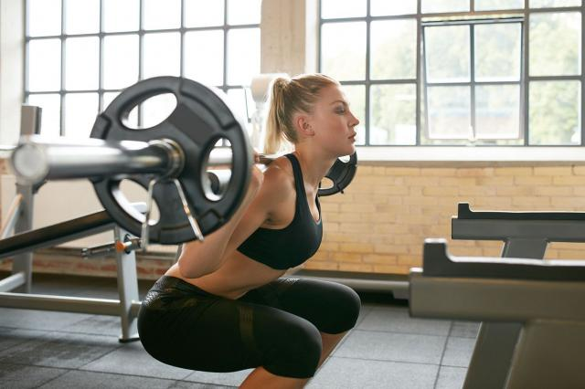 woman lifting weights in the gym with a spotter behind her,woman squatting weights