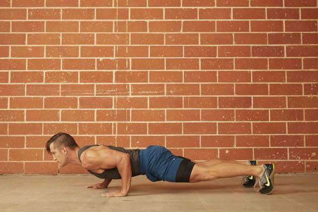 man demonstrating how to do a Staggered Hand Push-Up