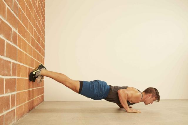 man demonstrating how to do a Feet on Wall Push-Up