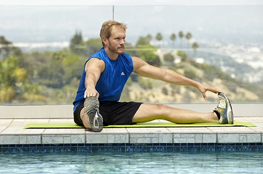 Man doing seated straddle stretch for better sex