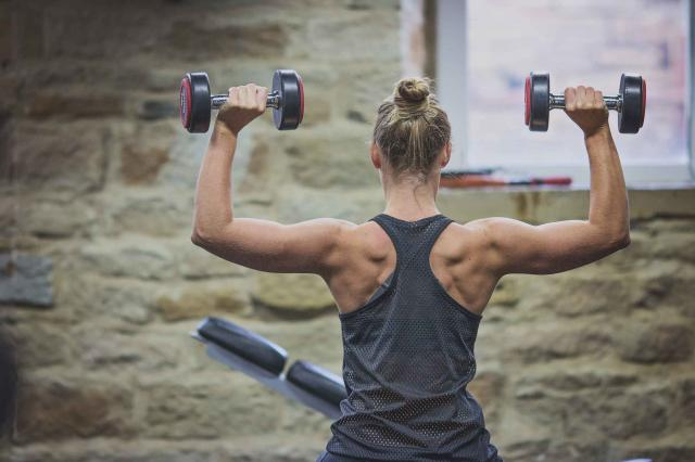 Young woman holding dumbells above her head seated down.
