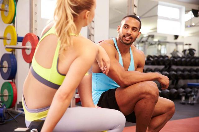 Young woman and man talking at a gym
