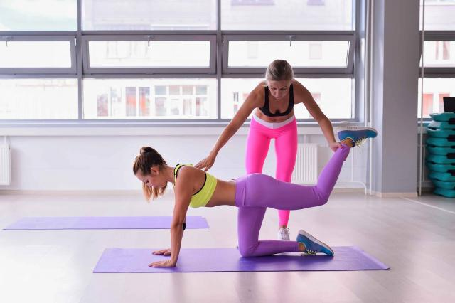 Personal trainer helping girl in stretching workout at gym fitness, yoga pose Sunbird