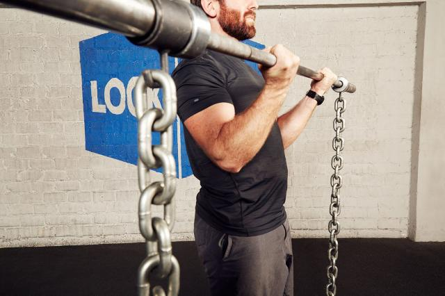 man lifting a barbell with chains