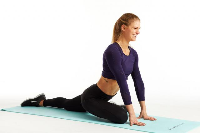 woman doing hip stretch on yoga mat