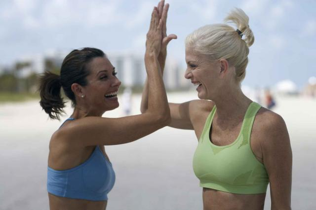 Two mature women on beach high fiving