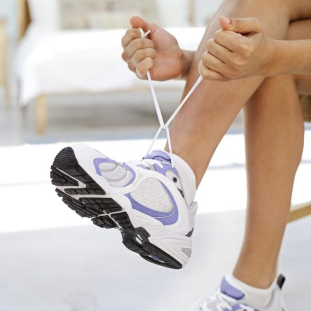 woman tying the laces on her sneakers